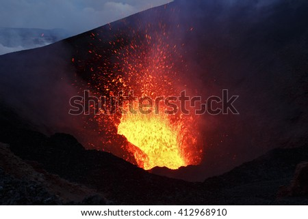 Beautiful night volcanic eruption - a view of the lava lake and a lava fountain, escaping from the crater. Erupting Tolbachik Volcano (Klyuchevskaya Group of Volcanoes). Russian Far East, Kamchatka. - stock photo