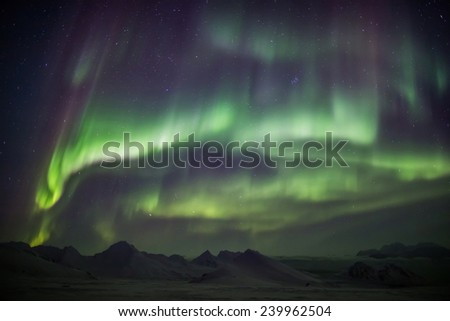 Beautiful Northern Lights across the sky - Arctic landscape - stock photo