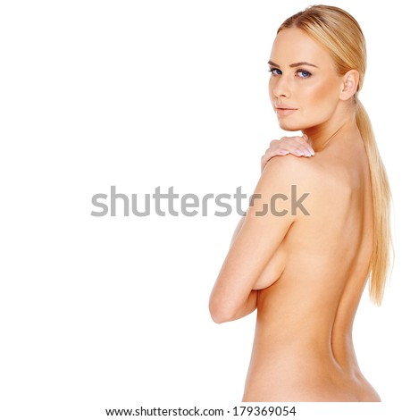 Beautiful nude blond woman standing sideways with her arm concealing her breasts looking back seductively over her shoulder at the camera isolated on white - stock photo