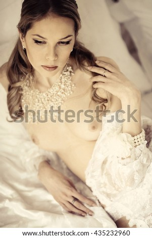 Beautiful nude sexy lady in elegant pose. Fashion portrait of girl indoors. Closeup beauty brunette woman with attractive body. Close up naked female model - stock photo