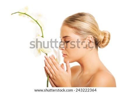 Beautiful nude woman holding orchid flower - stock photo