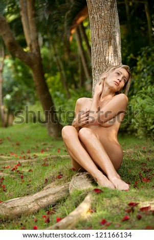 Beautiful nude woman in a nature environment, leaning on a tree trunk and hugging herself. - stock photo