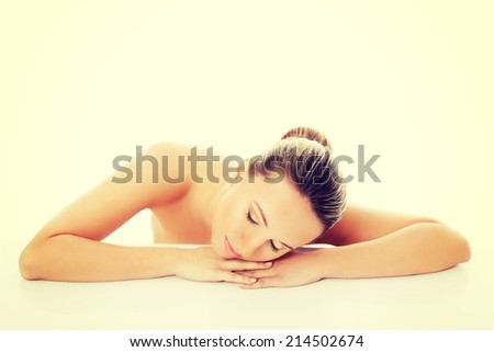 Beautiful nude woman is lying on her hands. Isolated on white.
