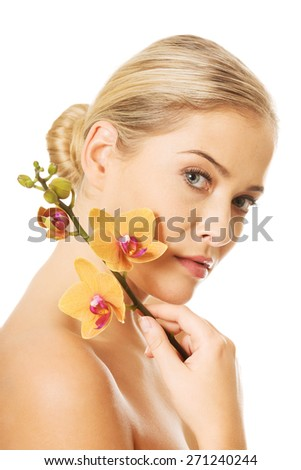 Beautiful nude woman with orchid flower - stock photo