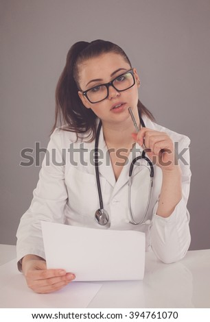 Beautiful nurse in white robe and black glasses is making her report and thinking about it at the table against of grey background