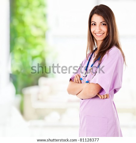 Beautiful nurse portrait standing in a clinic hall - stock photo