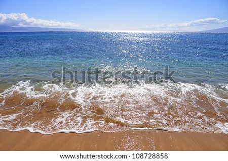 Beautiful ocean beach along west Maui's famous Kaanapali beach. Molokai and Lanai are  visible in the distance. - stock photo