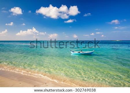Beautiful ocean beach an boat on Maldives - stock photo