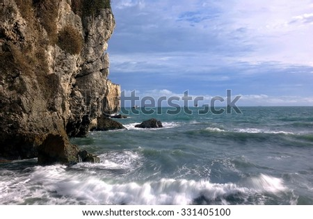 Beautiful ocean scene with steep cliff descending into the sea, on the horizon are several large ships. - stock photo
