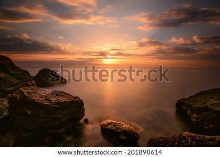 Beautiful ocean sunrise - calm sea and boulders stone coastline with unusual light - stock photo