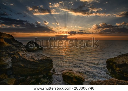 Beautiful ocean sunrise - calm sea and boulders  with sky sun rays and clouds - stock photo