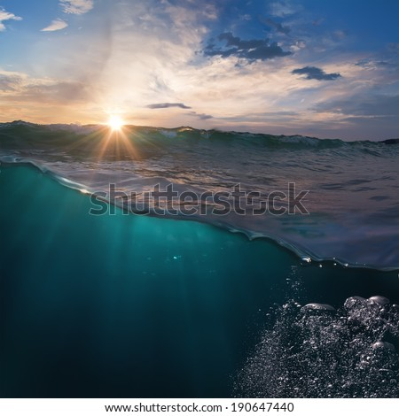 Beautiful ocean view with sunset behind breaking surfing wave over deep blue water for you design - stock photo