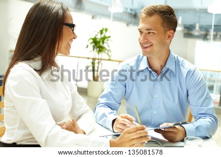 Beautiful office worker and her male colleague smiling at one another - stock photo