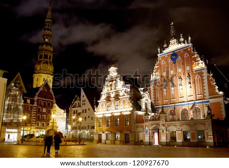 Beautiful old architecture of the central square of Riga. Night view with illuminated buildings and people silhouettes. - stock photo