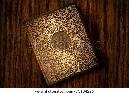 beautiful old book with gold ornamentation on a wooden table - stock photo
