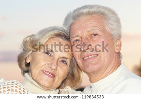 beautiful old couple standing in an outdoor setting