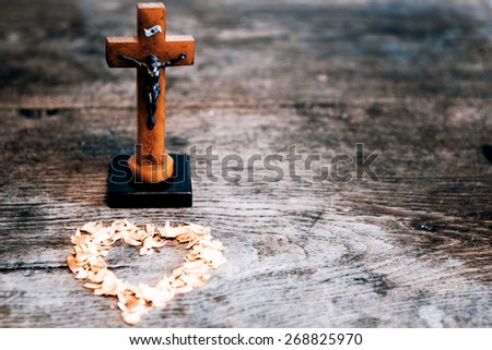 Beautiful old cross with jesus and yellow heart from leafs on the old wooden floor - stock photo