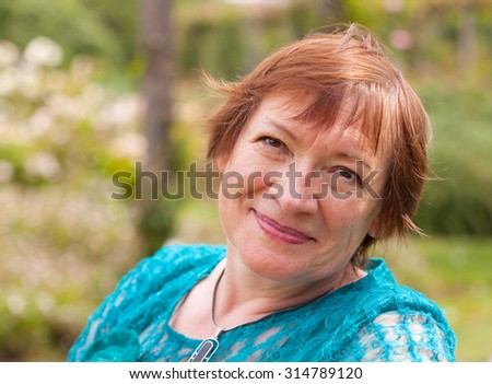 beautiful old lady in  park with blooming flowers - stock photo