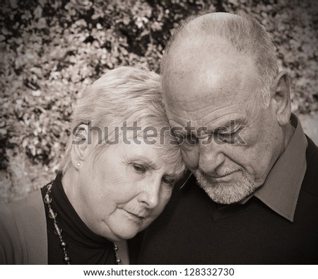 Beautiful old lady leaning on husbands shoulder in grief