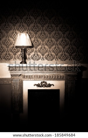 Beautiful old lamp on fireplace in red vintage room - stock photo