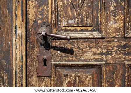 Beautiful old metal door handle with hand on an antique wooden door. - stock photo