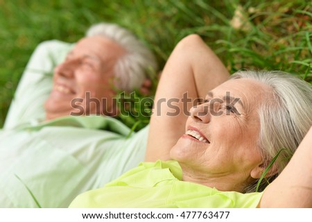 beautiful old people lying on the grass in the park