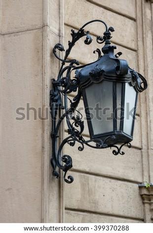 Beautiful old wall-lantern with ornamental wrought-iron bracket console - stock photo