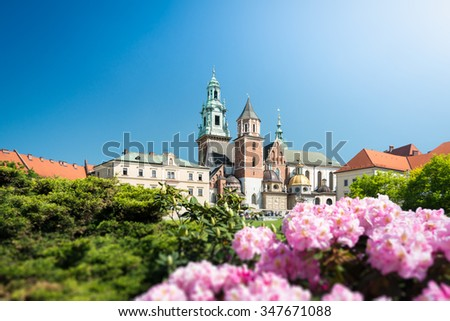 Beautiful old Wawel Cathedral in Krakow, Poland. Green trees and rose flowers surround medieval castle. - stock photo