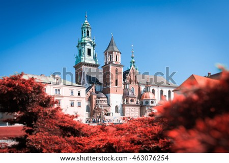 Beautiful old Wawel Cathedral in Krakow, Poland. Trees with red leaves surround medieval castle. Blue sky on summer day.