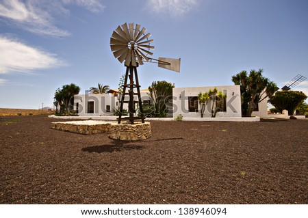 beautiful old windmill water tower on garden - stock photo