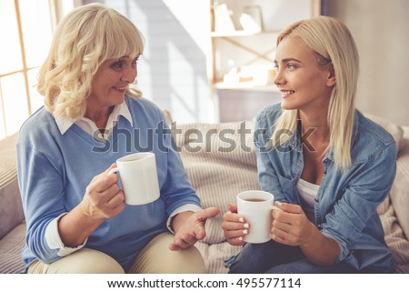 Beautiful old woman and young girl are drinking tea, talking and smiling while sitting on couch at home
