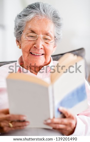 Beautiful old woman reading a book at home - stock photo