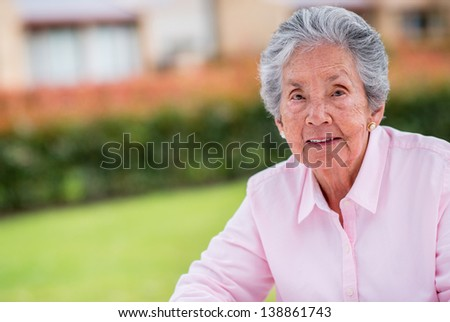 Beautiful old woman relaxing outdoors and looking happy
