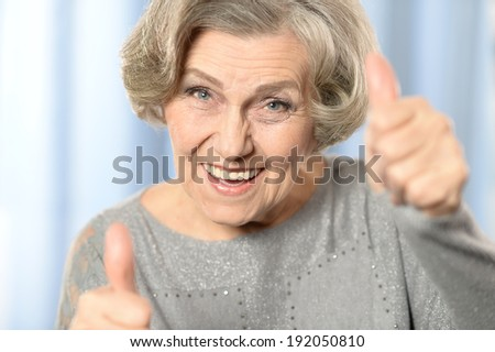 Beautiful old woman showing thumbs up on a blue background