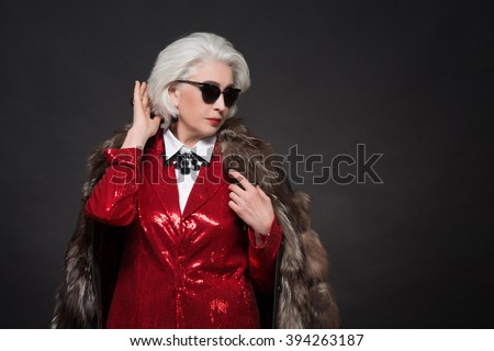 Beautiful old woman with blond hair wearing sunglasses. Fashionable lady in red business suit and expensive fur coat looking like Devil wears Prada.