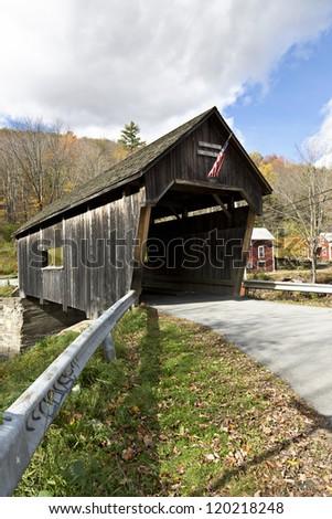 Beautiful old wooden covered bridge in Fall season - stock photo