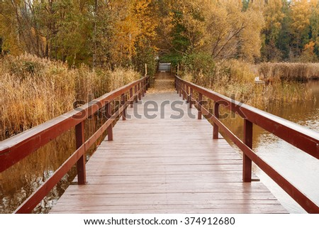 Beautiful old wooden pier, bridge for fishing and autumn forest in background. Picturesque natural landscape. Vacation concept. - stock photo