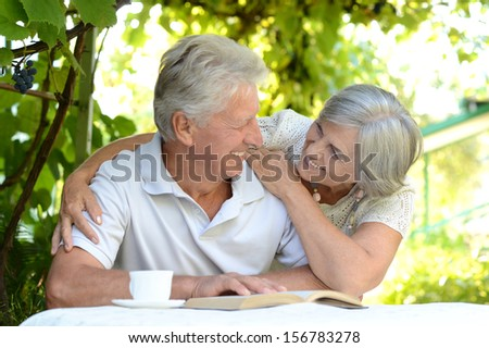 beautiful older couple resting in the garden in summer - stock photo