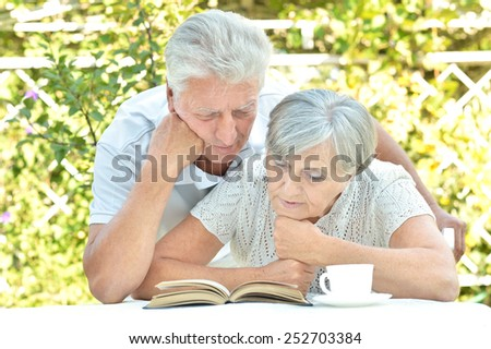 Beautiful older couple resting in the garden in summer ,reading a book - stock photo