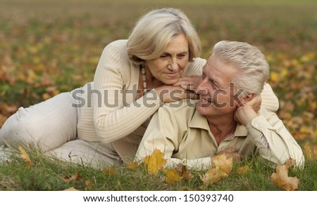 Beautiful older couple resting on a grass - stock photo