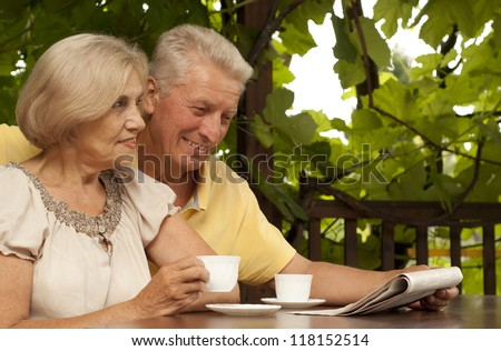Beautiful older couple sitting at a table at home on the veranda - stock photo