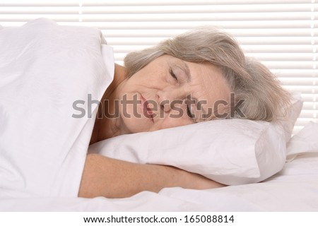 Beautiful older woman sleeping in the bedroom - stock photo