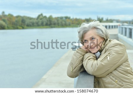 beautiful older woman walking in the park alone - stock photo