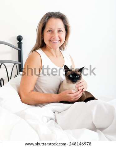 Beautiful older woman with   cat  on   bed. - stock photo