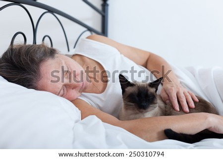 Beautiful older woman with   cat sleeping on   bed.