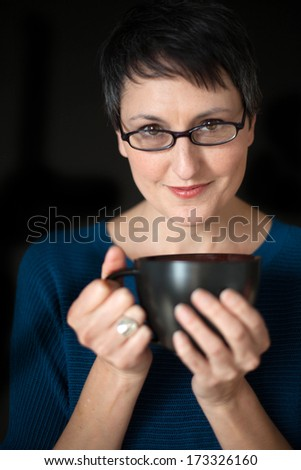Beautiful older woman with short brown hair and eyes, glasses, and coffee cup on a black background. - stock photo