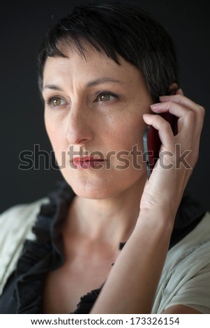 Beautiful older woman with short brown hair and eyes talking on a cell phone. - stock photo