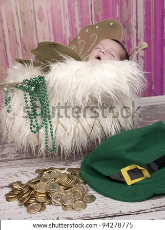 Beautiful one week old newborn sleeping with wings beautiful Irish Fairy Princess. The leprechaun has left behind his gold coins and hat. - stock photo