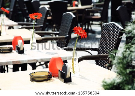 Beautiful open air summer restaurant tables with red flowers in vases - stock photo