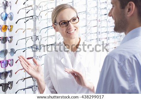 Beautiful optician and man choosing a new pair of glasses